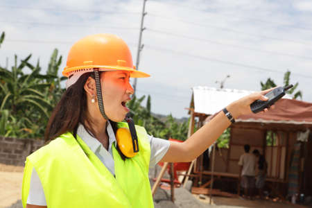 instructing: Pointing young Chinese female engineer with hardhat, directing and supervising a residential tropical construction site.