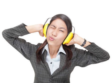 ironic: Ironic Asian businesswoman, winking and pouting lips, shutting out communication ostensibly by firmly pressing ear-protectors against her ears. Isolated over white with copyspace.