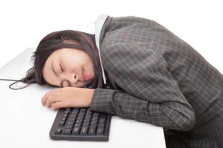 Young Asian office worker or businesswoman bored or stressed and sleeping face down on the keyboard sitting at her desk. Isolated over white.