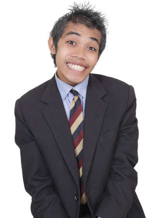 Young standing Asian businessman with a guilty childish smirking facial expression as if caught in an improper act and trying to make excuses. Isolated over white.