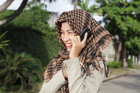 preppy: Attractively laughing happy Asian Muslim girl with headscarf or hijab and in formal jacket calling by cell phone outside on a tropical affluent residential street.