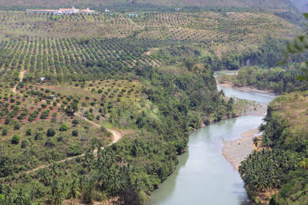 The meandering Cagayan river upstream from Cagayan de Oro City, Mindanao, Philippines, in a karst or limestone canyon and surrounded by hills and mango orchards belonging to an affluent farm or hacienda. Stock Photo