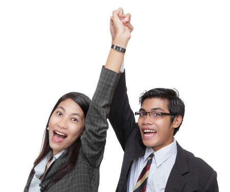 Two smiling and cheering corporate business team members (Asian man and woman), hands locked high over their head, celebrating success Isolated over white.
