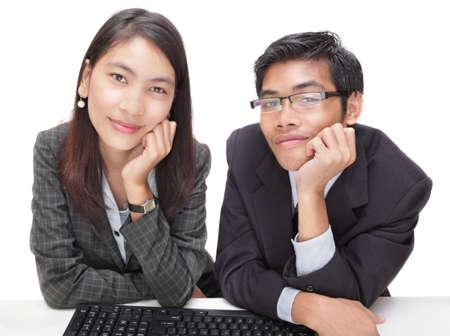receptivo: Dos sonriente y amigable buscando oficiales de ayuda o asistencia de cliente (Asia, macho y hembra) juntos en un teclado sentado en su escritorio. Aislado en blanco.