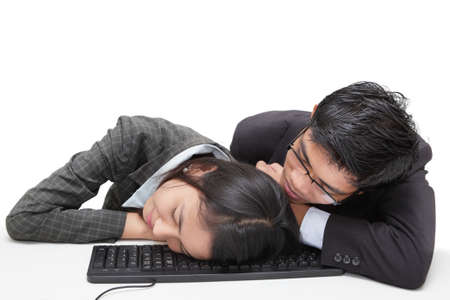 Two bored or overworked office workers (Asian, male and female) sleeping together on a keyboard sitting at their desk. Isolated over white. photo