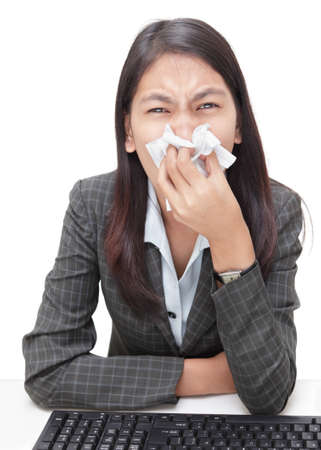 Asian young businesswoman in corporate outfit sneezing intensely in tissue or a handkerchief and blowing her nose on her desk, fighting a beginning flu or cold. Isolated over white. photo