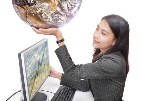 Happy young Asian businesswoman in corporate outfit sitting at her desk in front of her computer screen with spreadsheet data and holding up a globe. Isolated over white. Globe courtesy NASA/JPL. Stock Photo - 6960117