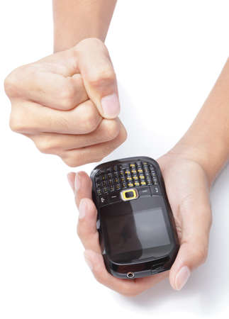 Male hand holding a cellphone and making a powerless and mad fist with his other hand after reception of a disturbing SMS text or MMS. Stock Photo