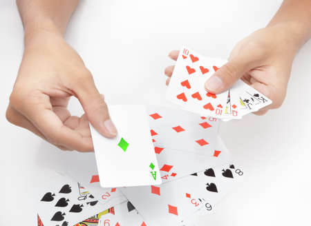 Hands holding and showing playing cards on white table background, playing the green ace card. Concept of ecology and conservation.