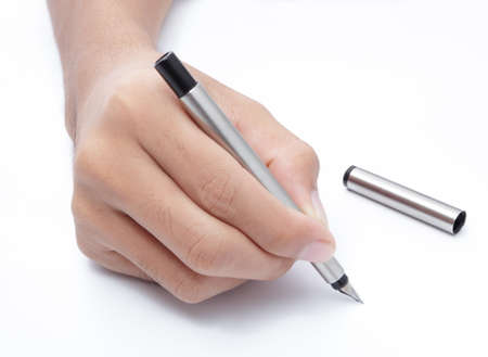 Cropped hand holding fountain pen, writing on blank seamless paper, with copy space. Focus on pen tip.