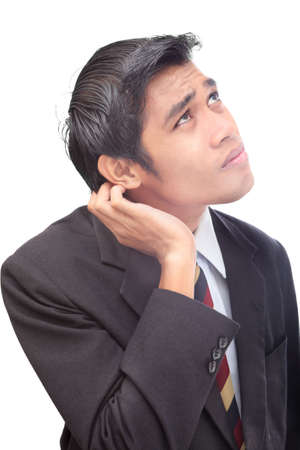 Insecure junior Asian businessman standing in doubt portrait, scratching his ear in conflict. Isolated over white.
