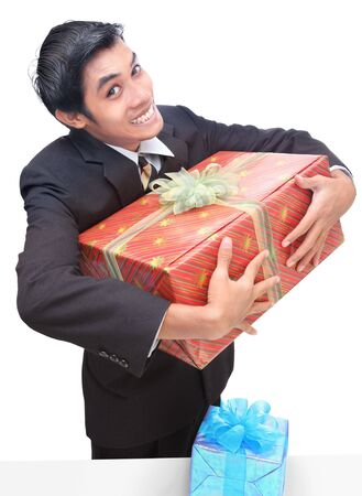 Latino junior businessman or office errand clasping or holding gift or present with smirky possessive grin or smile. Isolated over white.