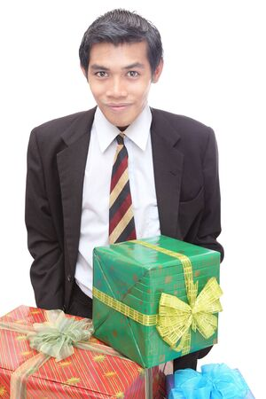 Young Latino professional businessman standing confidently and smiling behind colorful wrapped Christmas gifts or presents.