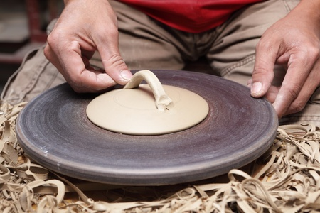 Close-up view of  potter's hands attaching ear or handle to the lid or cover of a clay vase or bowl in a pottery.