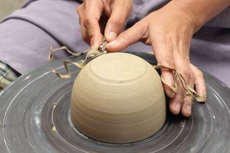 Potter's hands milling clay bowl on a turning wheel with a carving tool in a pottery, scraping excess clay off in curls. Zdjęcie Seryjne
