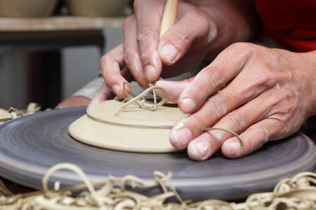 Potter's hands carving a groove at the bottom of a clay plate on a turning wheel with a carving tool in an Asian Philippines pottery.
