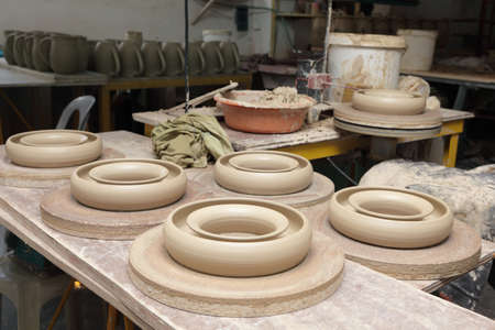 Overview of an Asian Philippines artisan pottery workshop with just finished wet clay kitchenware products right after shaping and before drying.