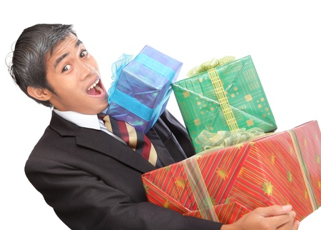 Latino surprised young businessman overwhelmed by a pile of presents or wrapped colorful Christmas gift boxes he can barely carry. Isolated over white.