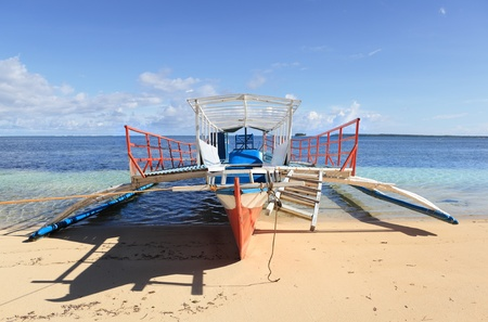 A typical local bangka outrigger vessel or boat as used for passenger and tourism transport in the Philippines: view on the beach with Pacific Ocean and tiny island in the background.