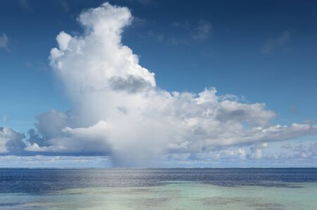 Large isolated cumulonimbus with rain shower at the base over the tropical  Pacific Ocean seen from the beach Zdjęcie Seryjne