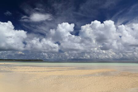 Panorama of tropical pristine paradise beach at low tide with rippled sand and impressive cloudscape.