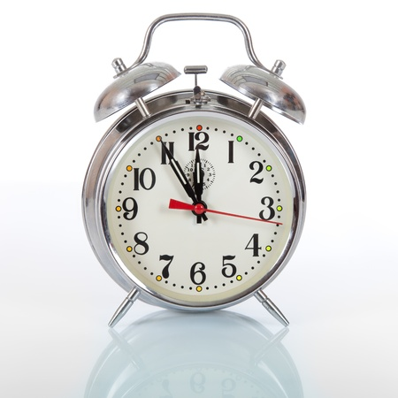 Old fashioned vintage mechanical alarm clock on white background with reflection, pointing five to twelve as a concept of urgency and pressing time.