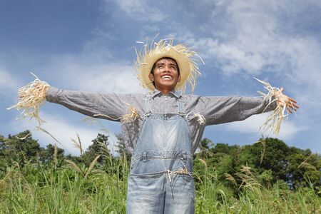 Laughing cheering human Asian scarecrow standing in field in dungarees with arms spread out and frayed hat against an azure sky in a summer landscape.