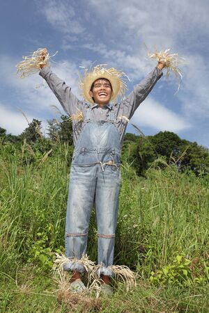 Laughing cheering human Asian scarecrow in dungarees wearing frayed hat standing full body in summer grass field with arms up triumphantly and in control.