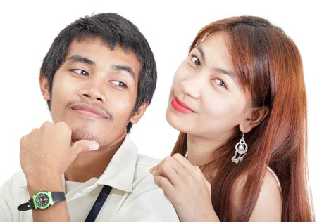 Close-up portrait of an Asian college youth couple bonding together in love or friendship, smiling. The guy looks amused to the girl while the girl looks dreaming and leaning with her hand on his shoulder. Isolated over white.