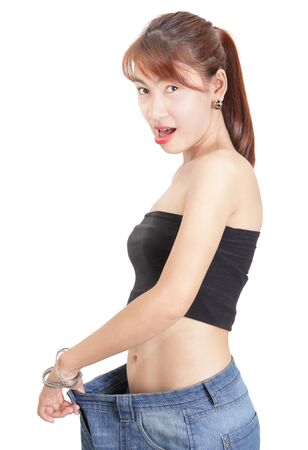 Asian slim fit girl or woman gazing amazed at her slimmed down waistline as proven by stretching her loose denim pants after a successful dieting or working out period. Isolated over white.
