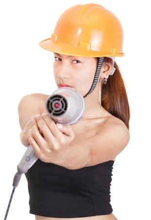 Asian (Japanese or Chinese looking) defiant and stern looking girl posing as engineer or foreman in sexy outfit with hardhat and aiming an hairdryer as a tool. Isolated over white.