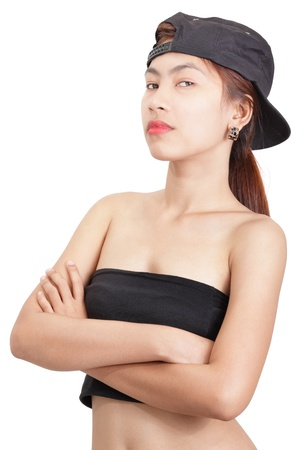 Portrait of dominant, stern and bossy Asian woman looking down in despise to camera with arms crossed, in sexy outfit and wearing a baseball cap. Isolated over white. Zdjęcie Seryjne