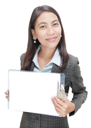 Smiling standing young congenial Asian businesswoman holding up an empty clipboard with pure white copyspace. Focus on eyes and left fingers. Isolated over white.