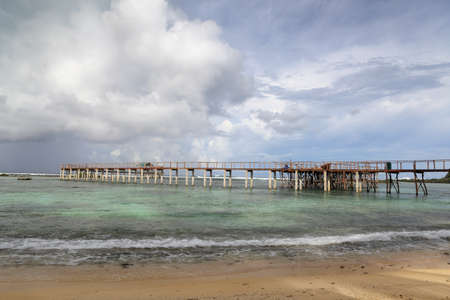 Wooden surfers walkway or pier and observation platform on the Cloud Nine surfing landmark at the tropical Pacific Ocean in Siargao Island, Philippines.