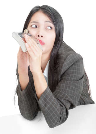 Young Asian businesswoman or office worker at her desk stealthily and sneakily drinking hard liquor or alcohol from a small flask, looking worried about getting caught. Concept of drinking and alcoholism on the job. Isolated over white. Stock Photo - 9229792