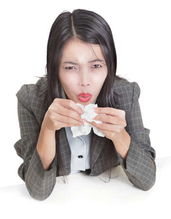 Young Asian businesswoman at her desk sneezing and feeling ill or with flu. Isolated over white. Zdjęcie Seryjne