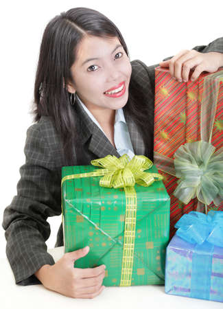 contended: Young contended and happy Asian businesswoman smiling at her desk holding a pile of (Christmas) presents. Isolated over white. Caveat at full size: one of the wrappings contains the word Christmas in fine print. Stock Photo
