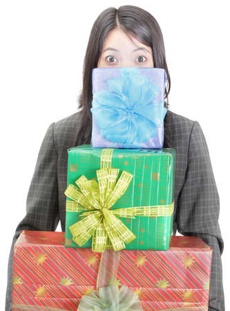 Young businesswoman standing and hiding behind a pile of colorful wrapped gifts she is carrying. Isolated over white. Caveat at full size: green box has �Christmas� text � focus on face, boxes slightly out of focus. Stock Photo - 9229797