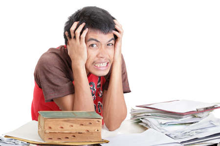 Desperate Asian student holding his hands on his head in despair with a hopeless grimace, overwhelmed by the mess on his desk and unable to get ready for exams by too many notes. Isolated over white.