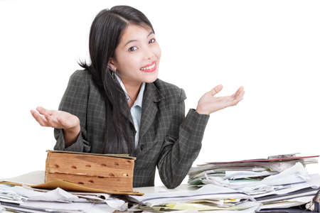 naive: Female secretary, office worker or businesswoman sitting at messy desk with a pile of paperwork stacked up, smiling in a silly way and not caring, raising her hands in a helpless and naive gesture suggesting non-commitment. Isolated over white.