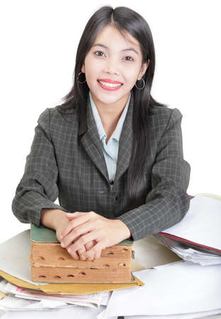 directory book: Asian professional businesswoman, adviser, councilor, real estate realtor or agent relying on old wisdom happy to give the best possible consulting advice. Confidently smiling at her desk holding an old book, directory or index. Isolated over white. Focus Stock Photo