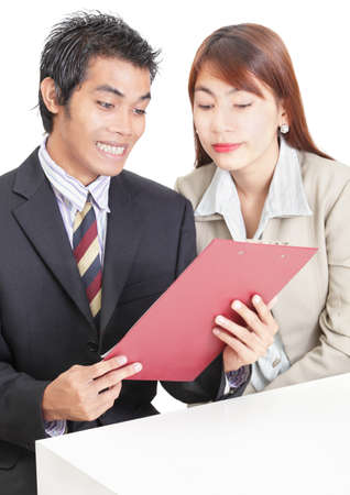 Asian young business steam (man and woman) on desk happily glancing at sales results. Plenty of copy space on desk for adding sheets and text. Isolated over white.