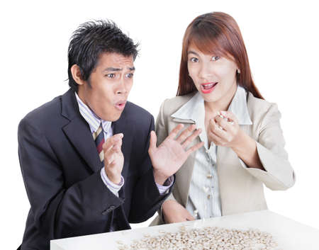 Young Asian business team at a desk illustrating the English idiom and metaphor of spilling the beans for betraying a secret or bringing out confidential information. The businesswoman spills the beans while the bewildered  businessman tries to stop her photo