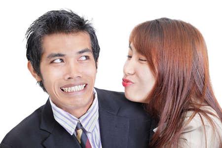 acoso laboral: Joven trabajador empresaria o la Oficina de Asia tratando de acercarse y besar a su colega masculino que aparente por su expresi�n facial reacio y avergonzado, parece que no les gusta su obertura. Retrato de d�o aislado en blanco. Concepto de acoso sexual un