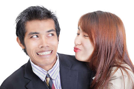 Young Asian businesswoman or office worker trying to approach and to kiss her male colleague that  apparent by his reluctant and embarrassed facial expression, seems to dislike her overture. Duo portrait isolated over white. Concept of sexual harassment a