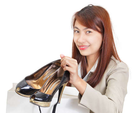Smiling young Asian Japanese-looking classy girl proudly showing fashionable high-heels shoes right out of the shopping bag. Isolated over white. Caveat at full size: focus on eyes, shoes out of focus.