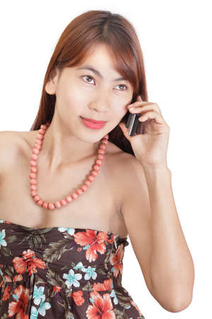 absent: Japanese-looking Asian girl or young woman in conservative flower dress calling by cellphone and listening with absent gaze. Isolated over white.