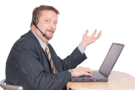 Proud middle-aged dominant manager or business leader in a conference call with headset sitting at his laptop PC, making a gesture of business or sales success, hand raised. Isolated over white.