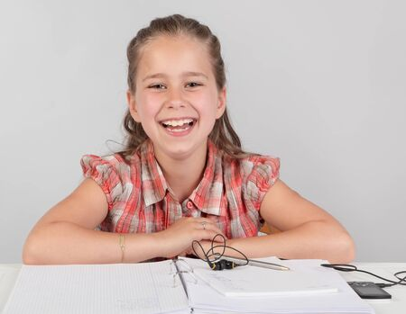 Portrait of young elementary school girl at a table with homework or assignment, happily laughing and cheering looking at cam. Zdjęcie Seryjne