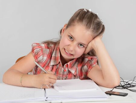 Portrait of young elementary school girl reluctantly making homework with a disliking facial expression.